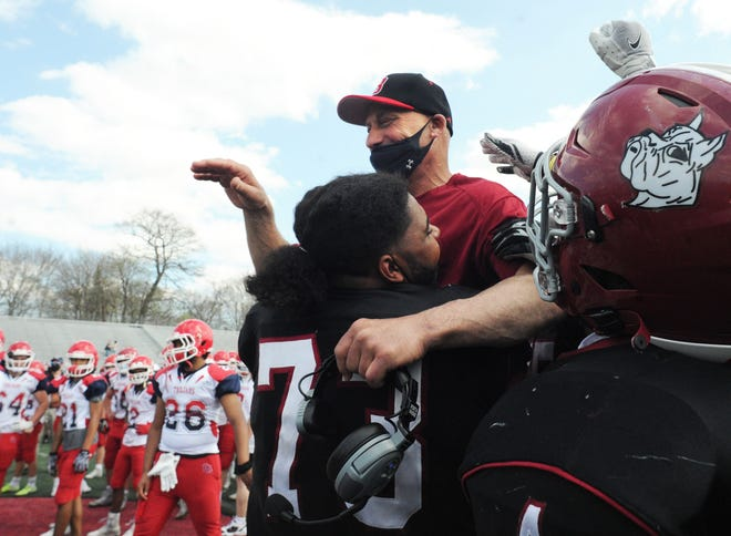Brockton High football coach Peter Colombo is hoisted into the air by his players at the conclusion of a game versus Bridgewater-Raynham, on Saturday, April 10, 2021.