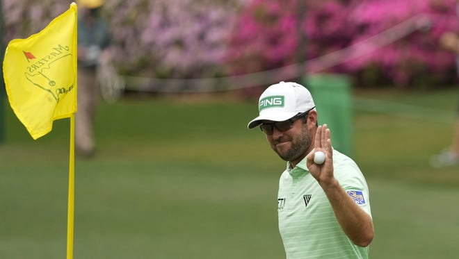 Corey Conners of Canada holds up his ball after a hole-in-one on the sixth hole during the third round of the Masters on Saturday. (AP Photo/Charlie Riedel)