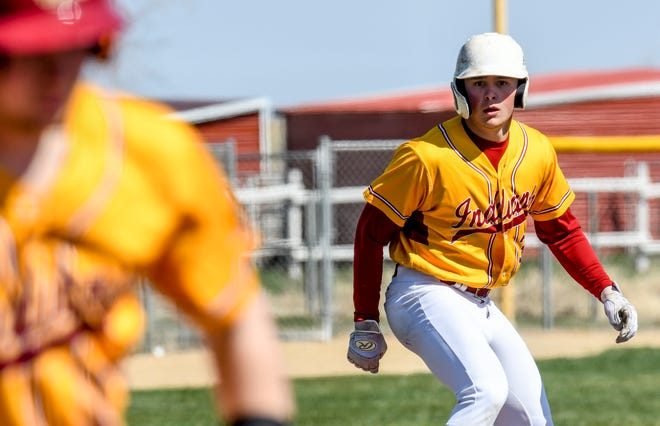 Hays High School's Dylan Dreiling leads off third base as teammate Dalyn Schwarz bats in the first inning of the first game of a doubleheader Friday against Garden City at Clint Lightner Field in Garden City.  The Indians scored seven runs in the first inning to open the game.