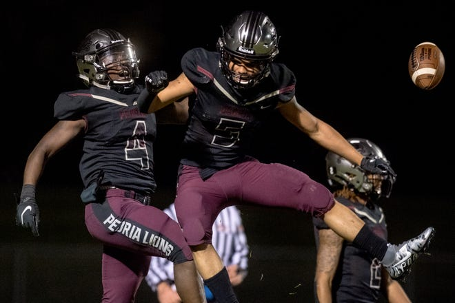 Peoria High's Rayshun Buckner (4) and Aziah Fisher (5) celebrate Buckner's touchdown against Bloomington High in the second half Friday, April 9, 2021 at Peoria Stadium.
