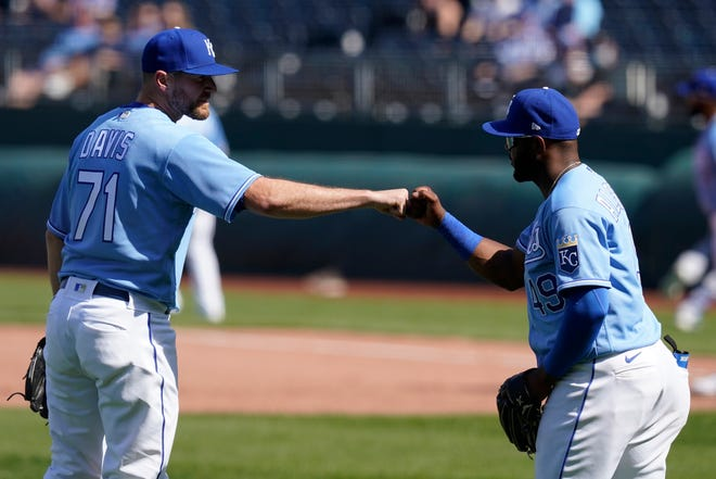 Kansas City  relief pitcher Wade Davis and third baseman Hanser Alberto bump fists after recording an out against Texas in the ninth inning on April 4.