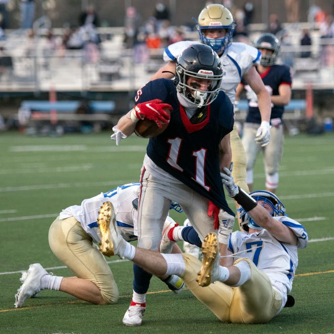 Lincoln-Sudbury junior Nolan O'Brien tries to get away from Acton-Boxborough senior John Hennessey during the game at Myers Field in Sudbury, April 9, 2021. The Warriors defeated Acton-Boxborough, 28-21. O'Brien added two punt returns for touchdowns in his team's win over Cambridge on Friday.