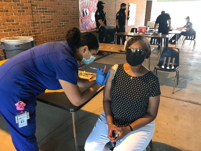 Heart of Florida Health Center Medical Assistant Jackie Zayas gives Carolyn McCorvey her second Pfizer shot Saturday at Reddick Collier Elementary School.