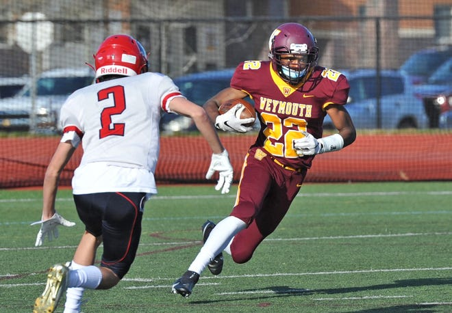 Weymouth running back Jaiden Remy, right, goes around Brookline defender Adrian Pinto during high school football action at Weymouth High School, Friday, April 9, 2021.