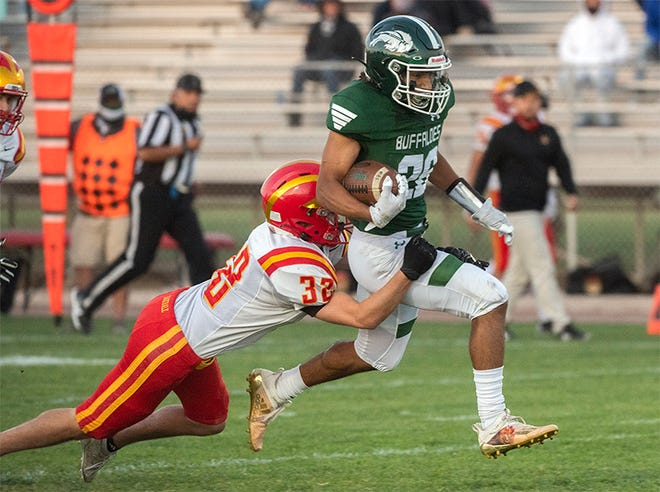 (4/9/21) Manteca's Lyon Colon, right, is brought down by Oakdale's Jake Kettering during a varsity football game at Guss Schmiedt Field in Manteca. CLIFFORD OTO/THE STOCKTON RECORD