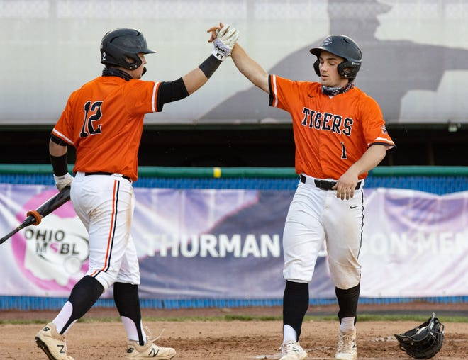 After scoring a run Massillon's Shane Rue (1) celebrates with Zach Catrone during their game against McKinley on Friday, April 9, 2021. (Special to The Canton Repository / Bob Rossiter)