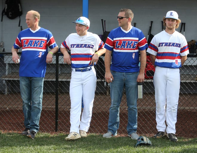Lake math teacher Dave Hudson (3) and baseball player Logan Brady (3), psychology teacher Tyler Six (4) and baseball player Koby Miller (4) watch festivities prior to their home game against Firestone on Friday, April 9, 2021. Each player selected teachers who have positively impacted their life.