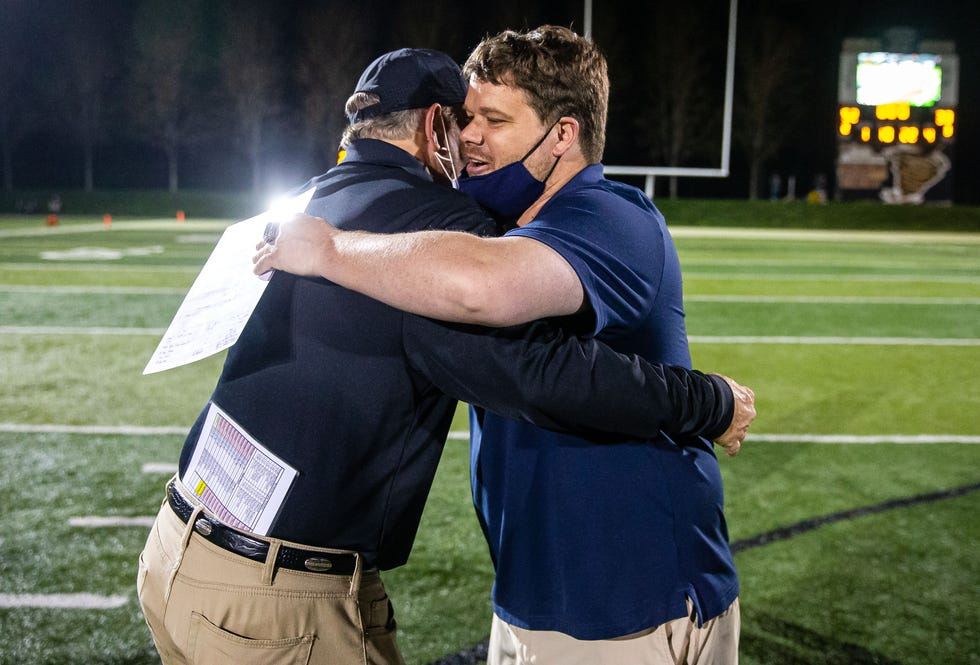 Rochester head football coach Derek Leonard hugs his father, Sacred Heart-Griffin head football coach Ken Leonard, after the Cyclones defeated the Rockets 52-33 at Ken Leonard Field in Springfield, Ill., Friday, April 9, 2021. [Justin L. Fowler/The State Journal-Register]