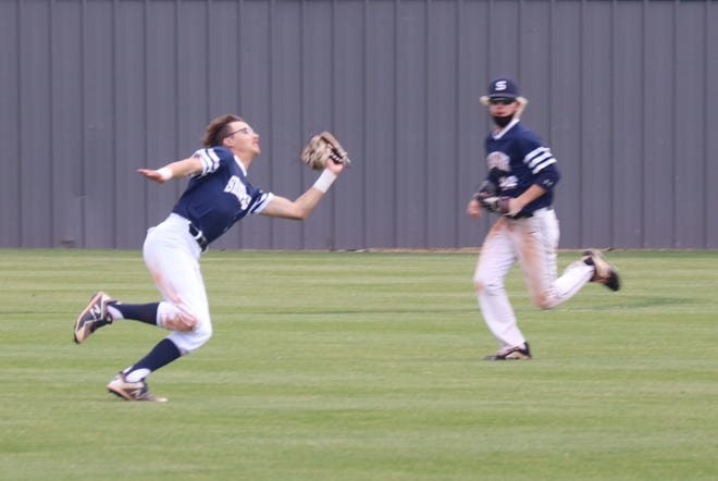 Shawnee left fielder Kasen Rogers (left) makes a lunging catch as teammate and center fielder Landon Steele backs up the play Friday against Harrah.