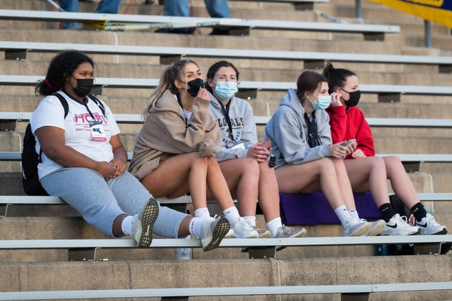 Masked fans enjoying the pleasant evening prior to the start of the Algonquin-Shrewsbury football game April 9.