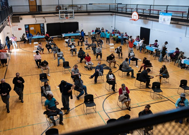 Newly-vaccinated Worcester residents wait in an YMCA gym during a walk-in equity COVID-19 vaccine clinic last week.