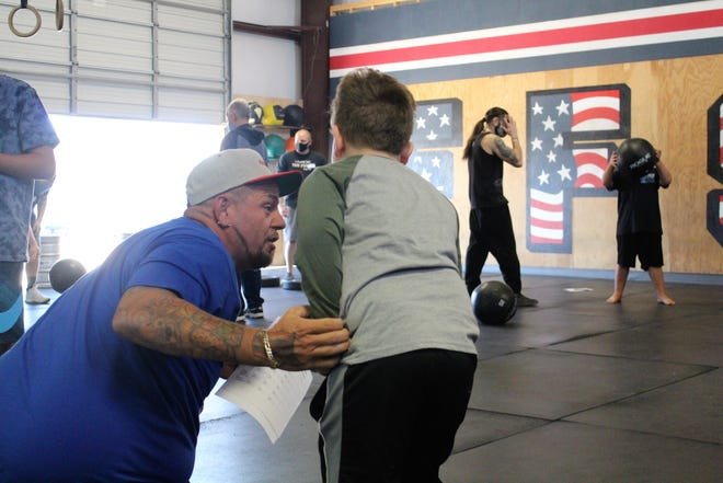 Kevin Blunt encourages Jayden Miller through a practice round at Autism MANA CrossFit, Saturday morning.