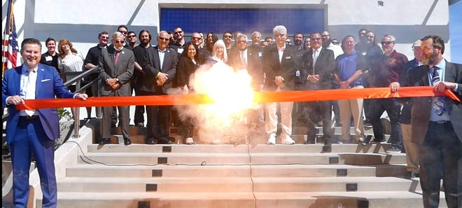 Exquadrum President Eric Schmidt, left, and CEO Kevin Mahaffy used a specially designed fuse cord to cut the ribbon on the rocket and technology company's new headquarters at the Southern California Logistics Airport in Victorville.