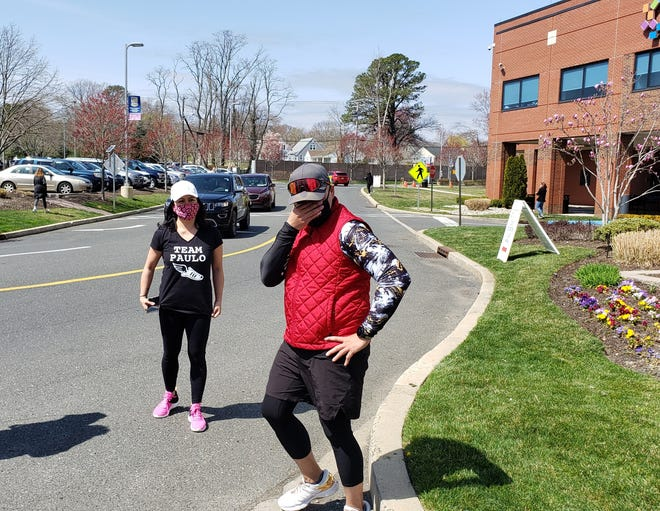 An overwhlemed Paulo Santos (in red) is greeted by wife Christine Santos (left) upon his arrival at Jersey Shore University Medical Center in Neptune after running 20 miles from CentraState Healthcare in Freehold Saturday.