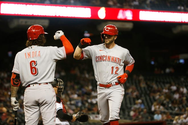 The Reds' Tyler Naquin (12) celebrates with Jonathan India after hitting a home run against the Diamondbacks during the home opener at Chase Field on April 9.