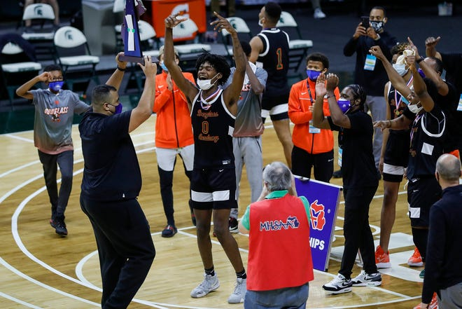 Detroit Douglass head coach Pierre Brooks Sr., left, lifts the championship trophy next to forward Javantae Randle (0) to celebrate the 47-41 win in the MHSAA Division 4 boys state final at the Breslin Center in East Lansing, Saturday, April 10, 2021.