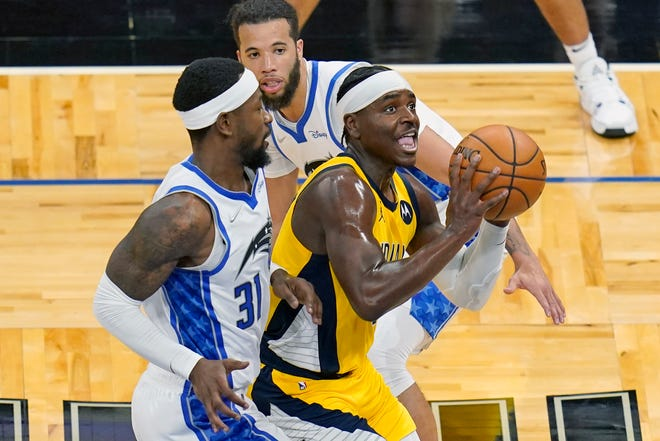 Indiana Pacers guard Aaron Holiday, right, shoots as he gets past Orlando Magic guards Terrence Ross, left, and Michael Carter-Williams during the first half of an NBA basketball game, Friday, April 9, 2021, in Orlando, Fla. (AP Photo/John Raoux)