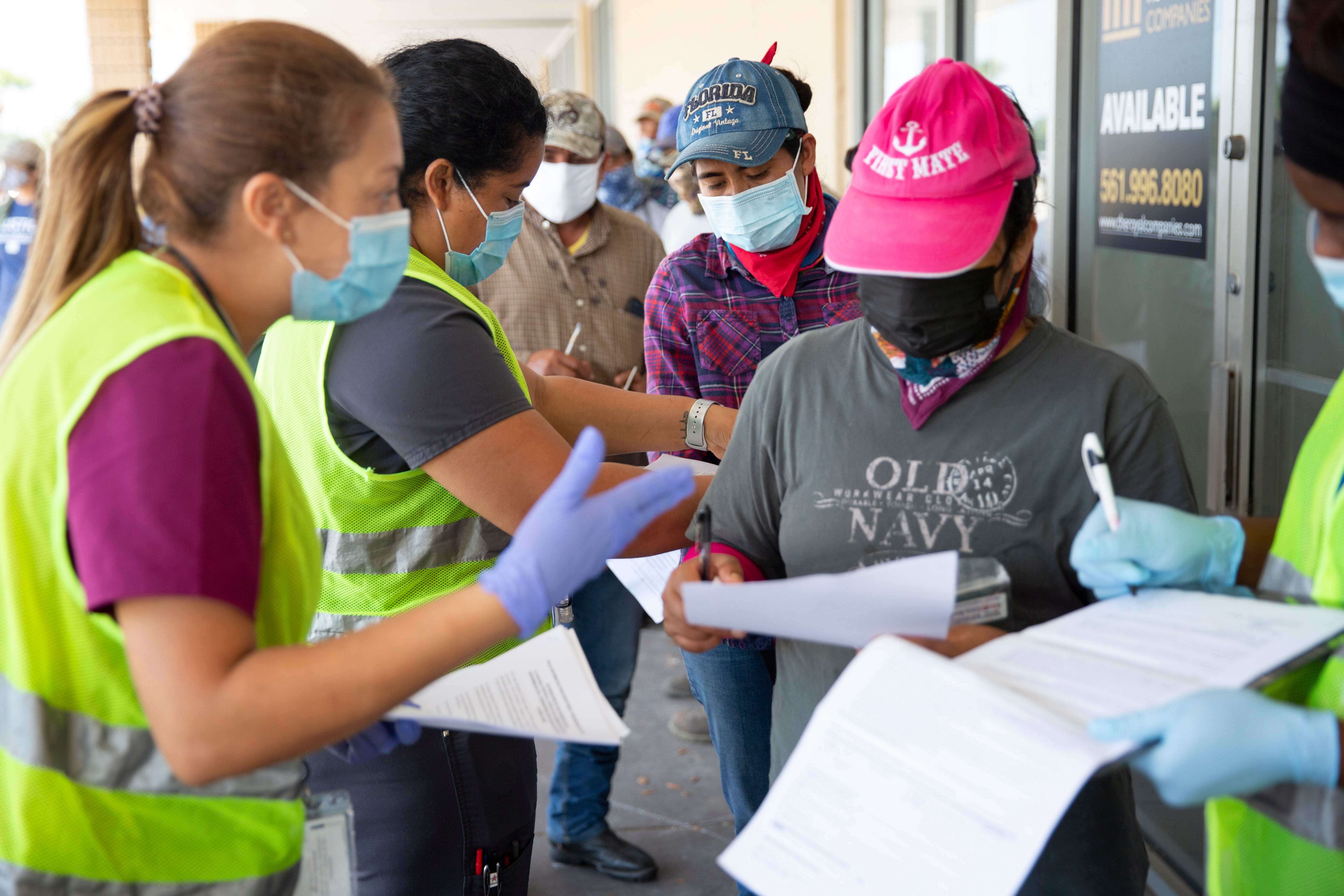 Healthcare Network employees help farmworkers fill out their paperwork as they wait in line during a vaccine clinic for farmworkers at the Florida Department of Health in Collier County site on Lake Trafford Road in Immokalee on Saturday, April 10, 2021.