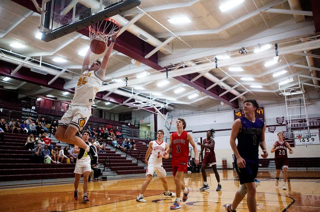 Berne Union's Brock Unger (24) hangs on the rim after slam dunking the ball during the Boys District 11 All Star Game at Newark High School in Newark, Ohio on April 9, 2021.