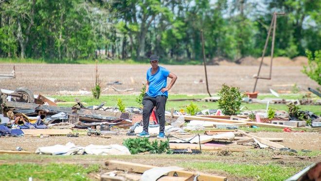 Gladus Johnson surveys the damage left behind by a deadly tornado in St. Landry Parish.