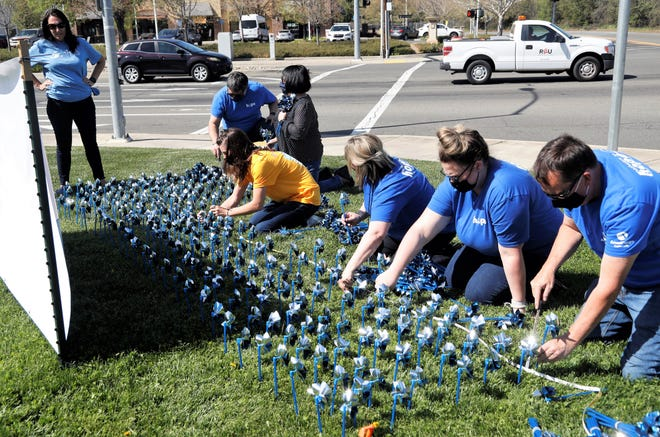 Members of Pathways to Hope for Children and the Redding Rancheria plant pinwheels on the lawn in front of Win-River Mini Mart in Redding on April 1, 2021, to kick off National Child Abuse Month. The group placed 753 pinwheels to represent the number of substantiated cases of child abuse in Shasta County during 2019.
