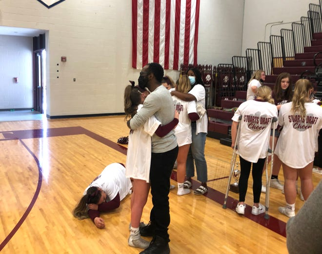 Donny Miller consoles a Stuarts Draft cheerleader after the team finished second in Region 2B competition cheer meet Saturday. With only one team advancing to states, the meet marked the end of Draft's season.