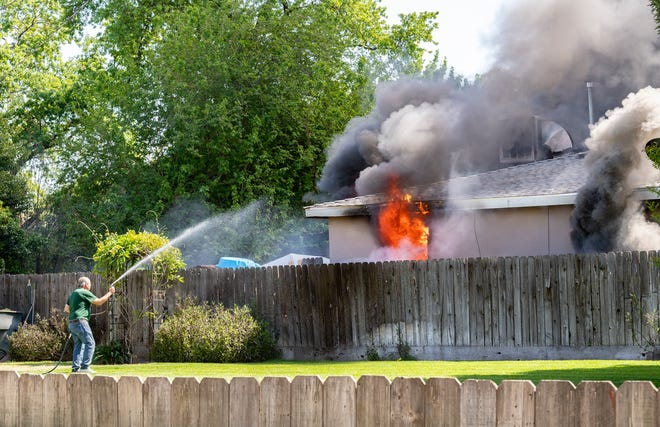 A neighbor sprays at a reported house fire in the 1500 block of South Central Street as Visalia fire and police departments respond Friday, April 9, 2021. No one was found in the rented home but the fire is being investigated as possible arson.