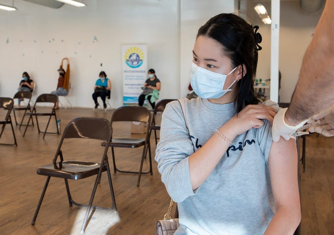 Julie Chen, 18, receives the Johnson & Johnson COVID-19 vaccine from Sovit Bista, owner of Auro Pharmacy, on April 11, 2021, in Austin, Texas. Auro Pharmacy and Open Eyes Beyond Border hosted the weekend event.