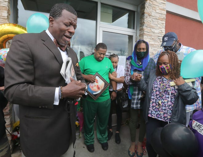 Minister Stephen Muhammad, left, leads friends, family and co-workers in prayer to remember Shawn Fann during a gathering at the Howe Avenue McDonald's on Sunday in Cuyahoga Falls. Police say Fann was shot and killed by another employee last week.