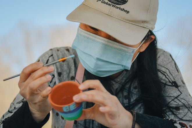 A woman paints a pot during the CoMo 200 Pop Up Parks 10 Days of Earth Day event Sunday afternoon at Indian Hills Park.