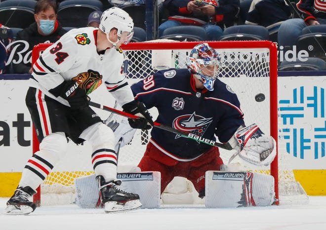 Columbus Blue Jackets goaltender Elvis Merzlikins (90) makes a save in front of Chicago Blackhawks center Carl Soderberg (34) during the third period of the NHL hockey game at Nationwide Arena in Columbus on Saturday, April 10, 2021.