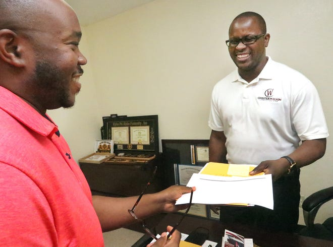 Chester Wilson Ed.D. , Executive Director of Outreach Community Care Network, at right, talks with staff member Ronald Jackson II.