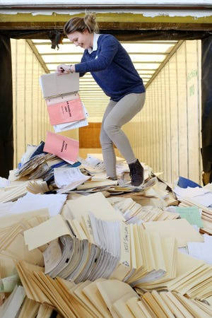 Evie Deery, 16, a sophomore at Notre Dame High School and member of the school's Leo Club, stands atop a pile of papers while emptying a binder, during the 20th annual Clean Out Your Files Day, Thursday April 12, 2018 at Area Recycles in West Burlington. Volunteers from the Burlington and Notre Dame High School Leo and ecology clubs helped unload paper and cardboard from vehicles.