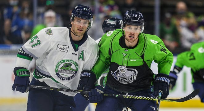 Florida Everblades defenseman Logan Roe (47), left, and Jacksonville Icemen forward Christopher Brown (10) watch the puck in play during the second period.
