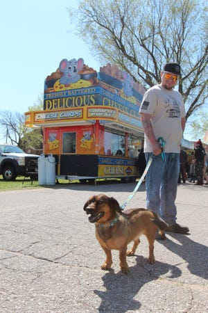 Hank looks for a snack with his owner, Straun Taylor, at Food and Tunes 2021 at the Kansas State Fairgrounds on Saturday.
