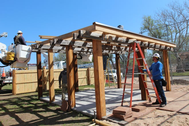 Evergy Green Team volunteer Tom Brockleman places a ladder as the group constructs an outdoor classroom on Saturday.