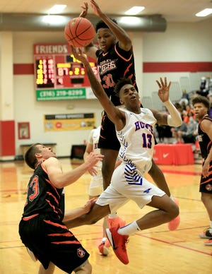 Hutchinson's Josh Baker shoots the basket against the defense of Cowley County's Josiah Harris (30) and Cevin Clark (13) during their NJCAA Region VI Championship game Saturday night at Friends University. Baker scored 24 points in the game. Hutchinson lost to Cowley County 116-107.