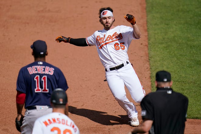 Baltimore Orioles' Ryan McKenna (65), a 2015 St. Thomas Aquinas High School graduate, slides into third base with a triple as Boston Red Sox third baseman Rafael Devers (11) looks on during the sixth inning Sunday, April 11, 2021, in Baltimore.