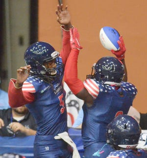 Salina Liberty quarterback Tyrie Adams (5) and running back Tracy Brooks (2) celebrate Brooks' first-quarter touchdown against the Ohama Beef on Saturday night at Tony's Pizza Events Center. The Liberty won, 39-14, to improve to 3-0 on the season.