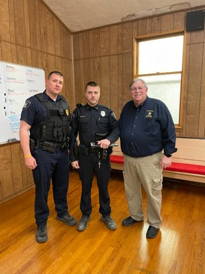Murrayville-Woodson police officer Patrick McKinnon (middle) received the Illinois Fraternal Order of Police (FOP) Life Saving Award during the Woodson Village Board meeting Monday, April 5. McKinnon was credited with saving the life of Thomas Lair after his truck flipped on Murrayville Road on March 26. At left is Murrayville-Woodson police chief Derek Suttles and at right is FOP State Lodge Awards Chair Jerry Lieb. [Fraternal Order of Police/ David Blanchette]