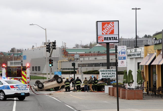 Worcester firefighters work near a car on its roof near Panera on Gold Star Boulevard. The crash occurred Sunday afternoon. It was not immediately known whether anyone was injured.