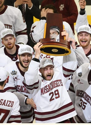 UMass forward George Mika (29) hoists the trophy and celebrates the Minutemen's 5-0 win over St. Cloud State for the NCAA Division 1 hockey championship.