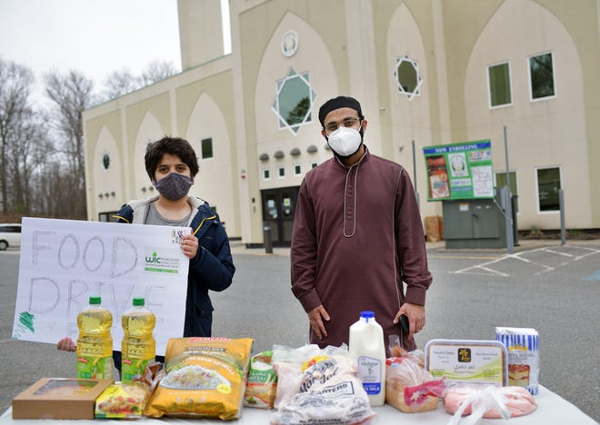 Asif Hirani, Imam at the Islamic Center, stands with Khalid Muttar, 13, and the display of food contained in each box during the food drive at Worcester Islamic Center Sunday.