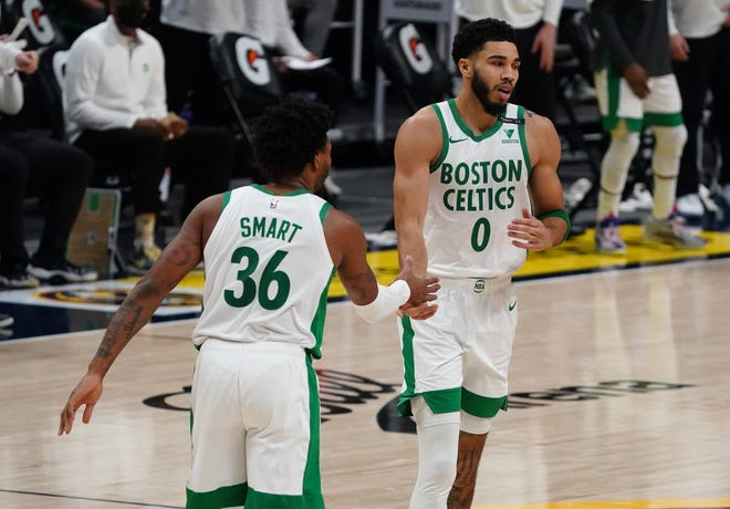 Celtics forward Jayson Tatum (0) celebrates his 3-pointer with guard Marcus Smart during the fourth quarter against the Nuggets.