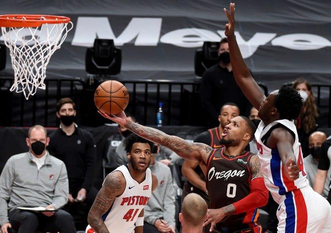 Guard Portland Trail Blazers Damian Lillard (0) membobol gawang pemain depan Detroit Pistons Sekou Doumbouya, kanan, selama babak pertama.