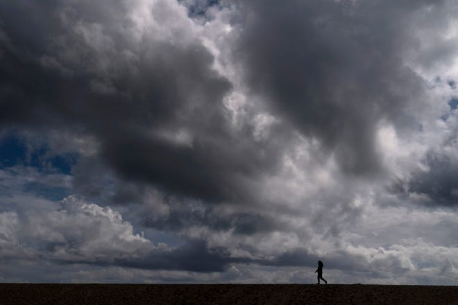 FILE - In this March 10, 2021, file photo, a woman strolls along the beach under rain clouds in Seal Beach, Calif. Rainstorms grew more erratic and droughts much longer across most of the U.S. West over the past half-century as climate change warmed the planet, according to a sweeping government study released, Tuesday, April 6, 2021, that concludes the situation in the region is worsening. (AP Photo/Jae C. Hong, File)