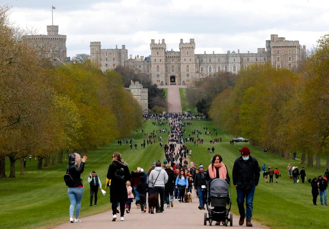 People walk on the long walk towards Windsor Castle, Windsor, England, Sunday, April 11, 2021, after the announcement of the death of Britain's Prince Philip on Friday. Britain's Prince Philip, the irascible and tough-minded husband of Queen Elizabeth II who spent more than seven decades supporting his wife in a role that mostly defined his life, died on Friday. (AP Photo/Frank Augstein)