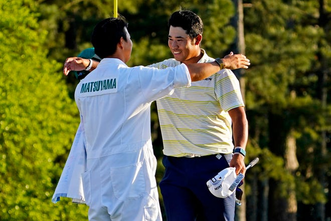 Hideki Matsuyama celebrates with his caddie Shota Hayafuji on the 18th green after winning the Masters on April 11.