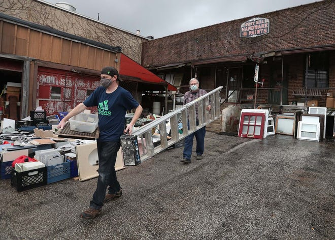 Richard Tschantz, right, the owner of West Hill Hardware in Akron, assists longtime customer Brian Cotrill carry a newly purchased ladder to his vehicle Monday. The family-owned store will close after 90 years in business.
