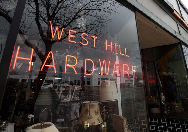 A neon sign is at the front entrance of West Hill Hardware on West Market Street in Akron.